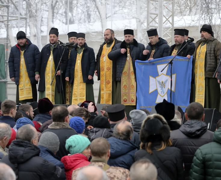 Orthodox priests speak to people gathered to support an independent Ukrainian church near the St. Sophia Cathedral in Kiev, Ukraine, Saturday, Dec. 15, 2018. Ukraine's Orthodox clerics gather for a meeting Saturday that is expected to form a new, independent Ukrainian church, and Ukrainian authorities have ramped up pressure on priests to support the move. (AP Photo/Efrem Lukatsky)