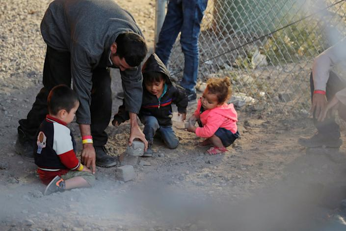 A man plays gives children rocks to play with inside an enclosure, where they are being held by U.S. Customs and Border Protection (CBP), after crossing the border between Mexico and the United States illegally and turning themselves in to request asylum, in El Paso, Texas, U.S., March 29, 2019. Photo: Lucas Jackson/Reuters)