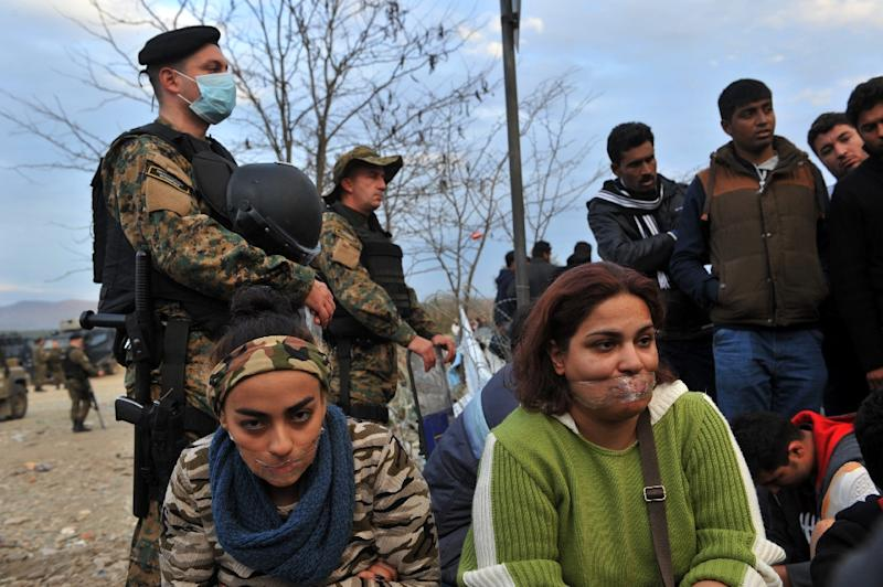 Women with their mouths closed with tape take part in a demonstration with other migrants and refugees as they wait to cross the Greek-Macedonian border near Idomeni on November 23, 2015 (AFP Photo/Sakis Mitrolidis)