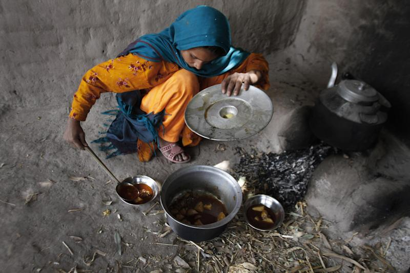 In this Thursday, June 28, 2012 photo, Raihana, 14, serves lunch at her home in Surkh Rod, district of Nangarhar east of Kabul, Afghanistan. For Razi Khan, a debt of almost $ 900 has condemned him and his family to years of work in a brick factory. With a salary of just $ 6 a day to feeds his eight children and sick wife, it is unlikely that he will soon pay off the debt that has followed him for the past six years. (AP Photo/Rahmat Gul)