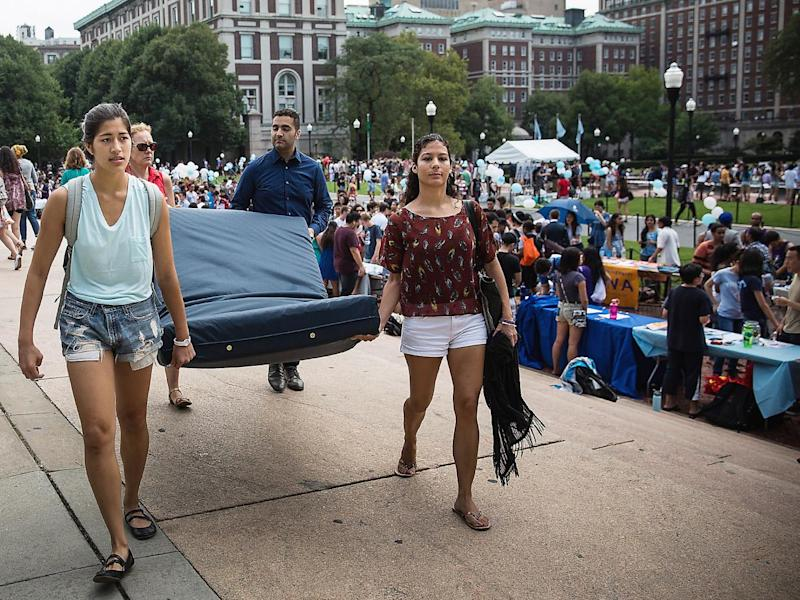Emma Sulkowicz (left), a student at Columbia University, carries a mattress in protest of the university's lack of action after she reported being raped (Getty)
