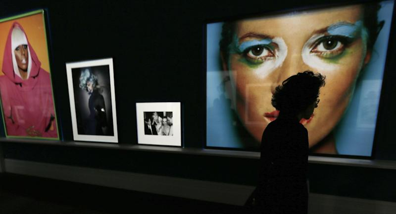 "A woman walks past a large portrait of Kate Moss, right, by photographer Mario Testino during the preview of his shows ""In Your Face"" and ""British Royal Portraits"" at the Museum of Fine Arts in Boston, Wednesday, Oct. 17, 2012. (AP Photo/Charles Krupa)"