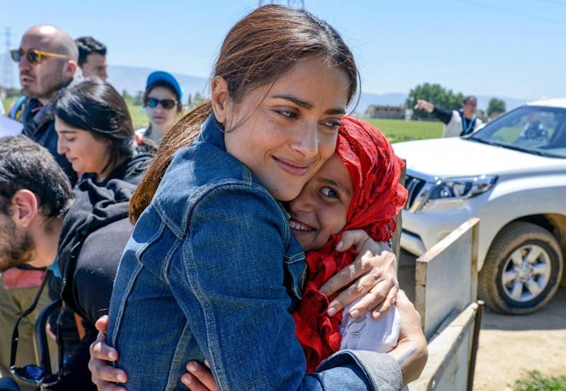 Handout picture released by UNICEF and taken on April 25, 2015, shows Mexican-US actress Salma Hayek (L) giving a hug to a young Syrian refugee at a camp in Lebanon's eastern Bekaa Valley as she campaigns with UNICEF to raise funds for refugees (AFP Photo/Sebastian Rich)