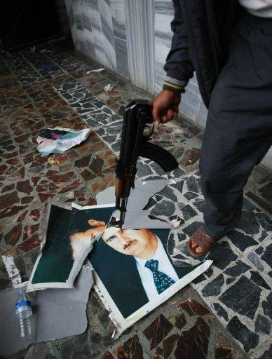 A Free Syrian Army soldier points a gun at a ripped portrait of President Bashar al-Assad at the Bab Al-Salam crossing