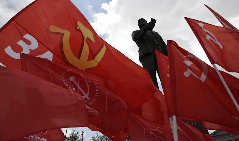 Communist party members hold flags near a monument to the Soviet Union founder Vladimir Lenin in the Crimean capital of Simferopol on May 6, 2014 (AFP Photo/Max Vetrov)