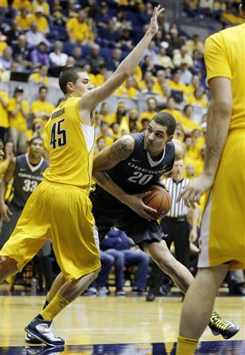 Oregon center Waverly Austin, right, looks for a way to the basket as California forward David Kravish, left, defends during the first half of an NCAA college basketball game Saturday, Feb. 2, 2013 in Berkeley, Calif. (AP Photo/Eric Risberg)
