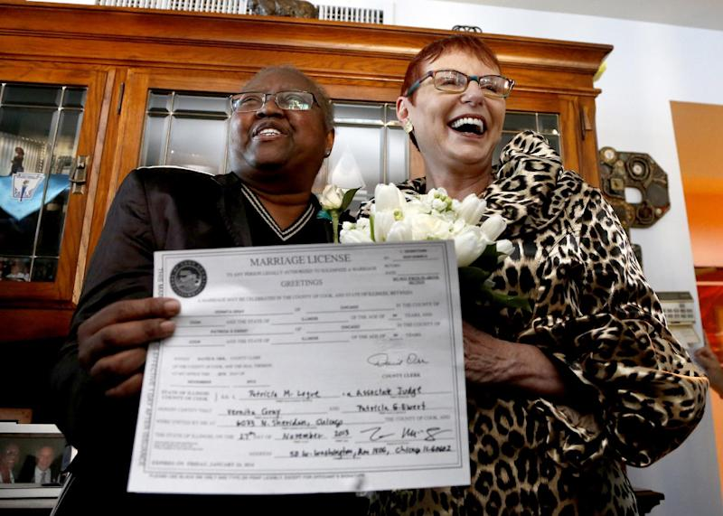 Holding their Illinois marriage license, Vernita Gray, left, and Patricia Ewert smile at friends after they were married by Cook County Judge Patricia Logue, the first gay marriage in Illinois, at the couple's home Wednesday, Nov. 27, 2013, in Chicago. U.S. District Judge Thomas Durkin on Monday, Nov. 25, 2013, ordered the Cook County clerk to issue an expedited marriage license to Gray and Ewert before the state's gay marriage law takes effect in June 2014, because Gray is terminally ill. (AP Photo/Charles Rex Arbogast)
