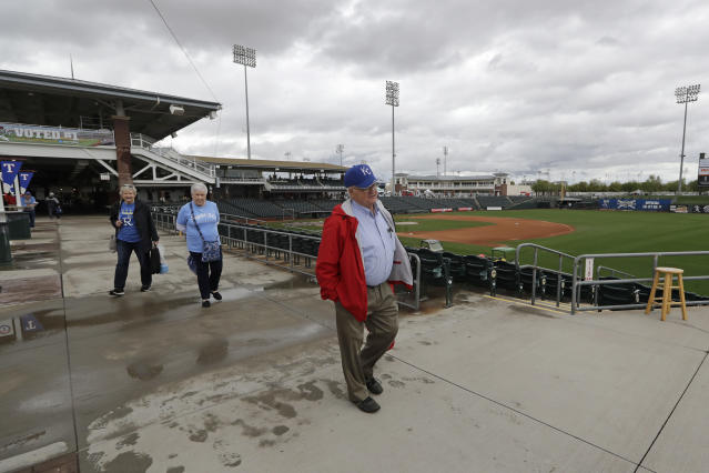 Kansas City Royals fans Ron Bennett, right, Donna Bogue and Kathy Bennett are among the last to head out of the ballpark after the cancelation of a spring training baseball game between the Royals and the Seattle Mariners Thursday, March 12, 2020, in Surprise, Ariz. Major League Baseball is delaying the start of its season by at least two weeks because of the coronavirus outbreak and has suspended the rest of its spring training game schedule. (AP Photo/Elaine Thompson)