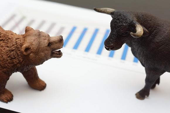 A bear figurine and a bull figurine face off, sitting on top of a piece of paper with a chart on it