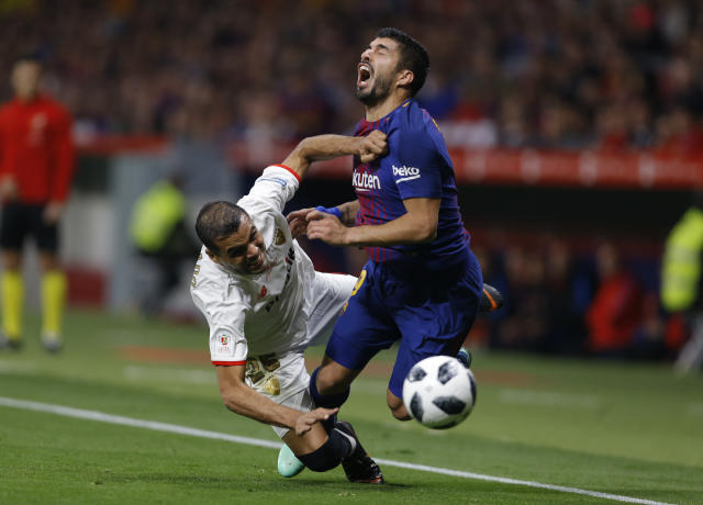 Sevilla's Gabriel Mercado, left, battles for the ball with Barcelona's Luis Suarez during the Copa del Rey final soccer match between Barcelona and Sevilla at the Wanda Metropolitano stadium in Madrid, Spain, Saturday, April 21, 2018. (AP Photo/Francisco Seco)