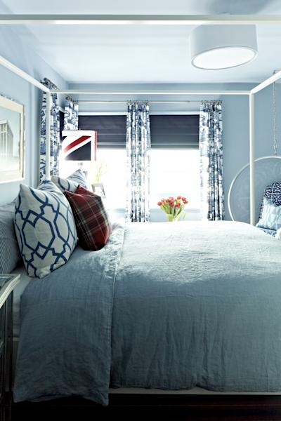 This publicity image released by Brian Patrick Flynn shows a bedroom designed with a blue-grey paint color called Drenched Rain from Dunn-Edwards. The bed, with washed linen, adds a lived in, casual look. Flynn often layers washed out blue tones with navy and white to create a summer-inspired aesthetic. (AP Photo/Brian Patrick Flynn, Daniel Collopy)