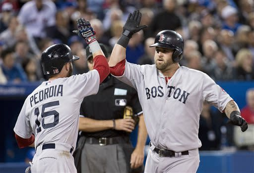 Boston Red Sox's Mike Napoli, right, celebrates his two-run home run with teammate Dustin Pedroia, left, while playing against the Toronto Blue Jays during fifth-inning baseball game action in Toronto, Friday, April 5, 2013. (AP Photo/The Canadian Press, Nathan Denette)