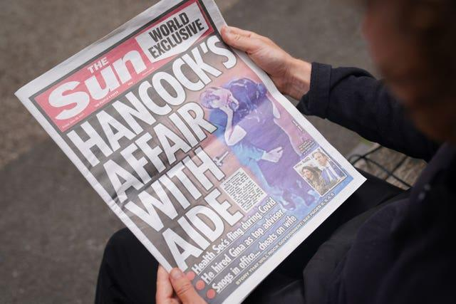 A person reads a copy of Friday's Sun newspaper, with the story and pictures of Health Secretary Matt Hancock appearing to kiss his adviser Gina Coladangelo