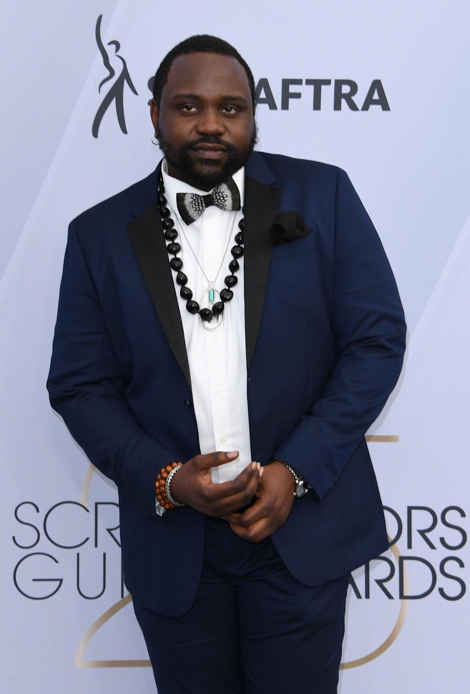 <p>Wearing a navy suit with a bow tie and black necklace. </p>