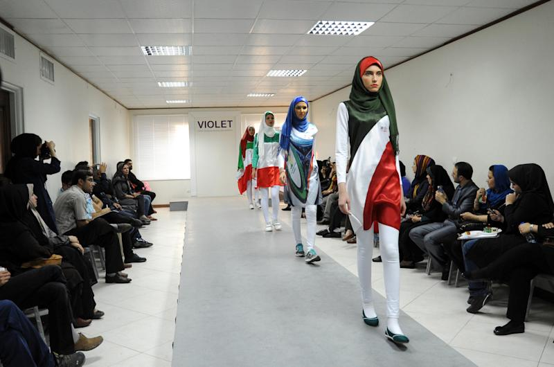 Iranian models present outfits bearing the national flag's colors and other World Cup-linked designs in Tehran on June 24, 2014 (AFP Photo/Bahareh Asadi)