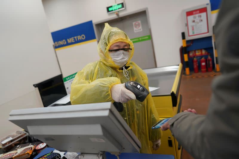 Worker scans a customer's mobile phone for payment at a checkout counter inside a supermarket, as the country is hit by an outbreak of the novel coronavirus, in Beijing