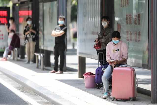 People wait at a bus station in Wuhan in China's central Hubei province on Monday (AFP via Getty Images)