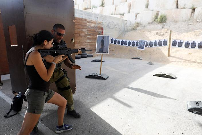 "<p>An Israeli instructor guides a tourist as she fires a rifle during a two hour ""boot camp"" experience, at ""Caliber 3 Israeli Counter Terror and Security Academy"" in the Gush Etzion settlement bloc south of Jerusalem in the occupied West Bank July 13, 2017. (Photo: Nir Elias/Reuters) </p>"
