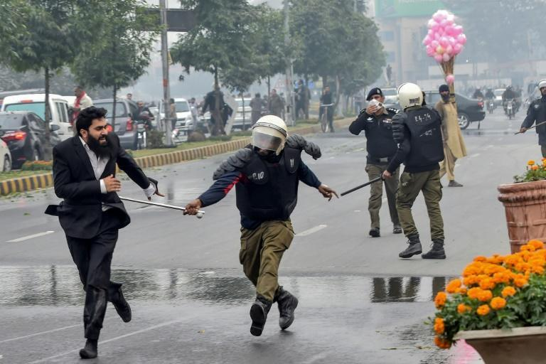 A policeman chases a lawyer following the clash at a Lahore cardiac hospital