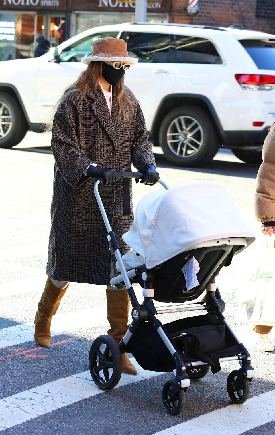 """This day, Gigi opted for the <a href=""""https://www.teenvogue.com/story/gigi-hadid-stroller-style?mbid=synd_yahoo_rss"""" rel=""""nofollow noopener"""" target=""""_blank"""" data-ylk=""""slk:perfect mix of luxury and affordable fashion"""" class=""""link rapid-noclick-resp"""">perfect mix of luxury and affordable fashion</a> combining a coat from Mango, Dear Frances boots, and a Louis Vuitton bucket hat that she can't seem to get enough of."""