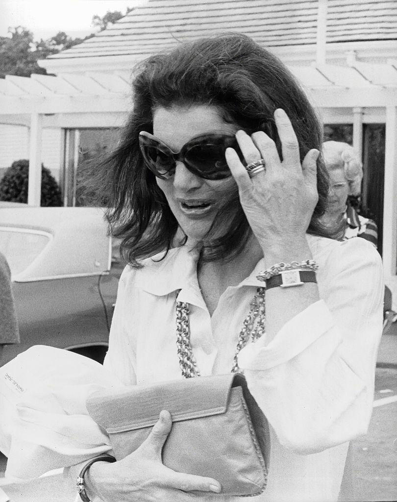 <p>Jackie's classic button-downs were always dressed up with well-placed jewelry, like her gold chain layered necklace and matching bracelet, oversize bangle, and Cartier Tank timepiece. And, of course, we can't forget her signature sunglasses. <br></p>