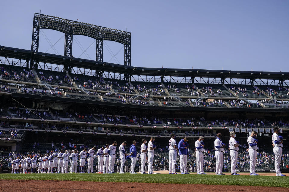 The New York Mets stand for pre-game ceremonies before their home-opening baseball game against the Miami Marlins, Thursday, April 8, 2021, in New York. (AP Photo/John Minchillo)