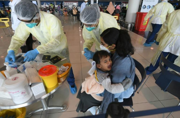 Health workers take a blood test from a child carried by an Indian woman at the Dubai International Airport before they leave the Gulf Emirate on a flight back to their country on May 7, 2020 (AFP Photo/Karim SAHIB)