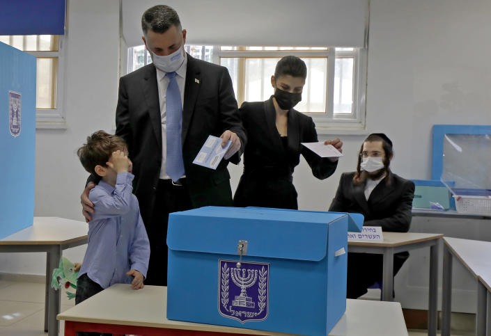 Chairman of Israel's New Hope party Gideon Saar and his wife Geula vote with their children at a polling station during Israel's fourth national election in the coastal city of Tel Aviv Tuesday, March 23, 2021. Israelis began voting on Tuesday in the country's fourth parliamentary election in two years, a highly charged referendum on the divisive rule of Prime Minister Benjamin Netanyahu. (Jalaa Marey/Pool Photo via AP)