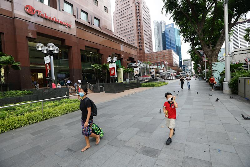 SINGAPORE - MARCH 24: People walk past the Takashimaya shopping centre in an unusually quiet Orchard Road on March 24, 2020 in Singapore. Singapore will not allow short term visitors to enter or transit through the country from March 24 to contain the spread of the imported COVID-19 infection. (Photo by Suhaimi Abdullah/Getty Images)