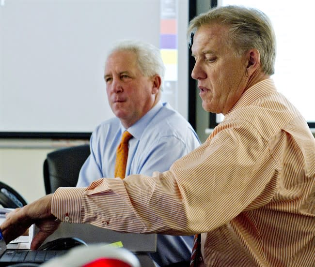 In this photo provided by the Denver Broncos, head coach John Fox, rear, and executive vice president of football operations John Elway, right, monitor the NFL football draft in the Broncos' draft room, Thursday, April 26, 2012, in Englewood, Colo. (AP Photo/Denver Broncos, Eric Lars Bakke)