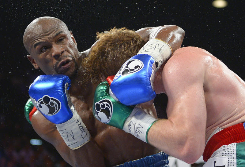 """FILE - In this file photo taken Saturday, Sept. 14, 2013 Floyd Mayweather Jr., left, gets tangled up with Canelo Alvarez during a world light-middleweight title fight, in Las Vegas. Mayweather Jr. will arrive in South Africa on Wednesday, Jan. 15. 2014, for a six-day visit that the government hopes will help """"resuscitate"""" boxing in the country. (AP Photo/Mark J. Terrill-File)"""