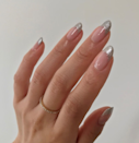 """Not only do silver tips add an icy touch; they make nails look insanely long. Try Ella + Mila polish in <a href=""""https://shop-links.co/1724788917663364819"""" rel=""""nofollow noopener"""" target=""""_blank"""" data-ylk=""""slk:Moonshadow"""" class=""""link rapid-noclick-resp"""">Moonshadow</a> for the glittering tips."""