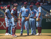 Philadelphia Phillies' Jake Arrieta, center, looks on with his teammates as he waits to be pulled from the game during the fifth inning of a baseball game against the San Francisco Giants, Thursday, Aug. 1, 2019, in Philadelphia. (AP Photo/Chris Szagola)
