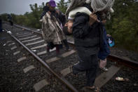 <p>Bara'ah Alhammadi, 10, a Syrian migrant, is carried on the back of her father as they make their way along a railway track after crossing the Serbian-Hungarian border near Roszke, southern Hungary, Sept. 11, 2015. (Photo: Muhammed Muheisen/AP) </p>
