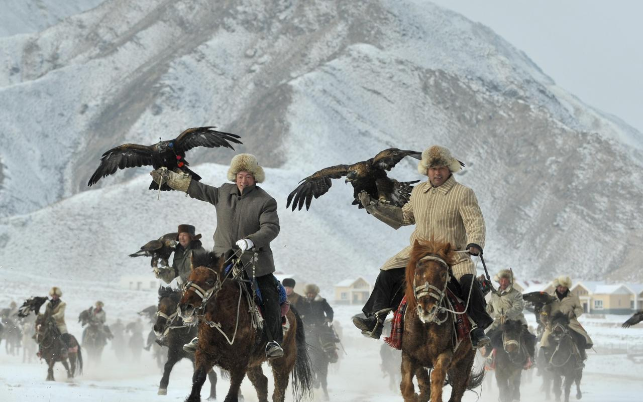 Herdsmen from the Kyrgyz ethnic group hold their falcons as they ride on horses during a hunting competition in Akqi county, Xinjiang Uighur Autonomous February 1, 2015. Picture taken February 1, 2015. REUTERS/Stringer (CHINA - Tags: ANIMALS SOCIETY TPX IMAGES OF THE DAY) CHINA OUT. NO COMMERCIAL OR EDITORIAL SALES IN CHINA