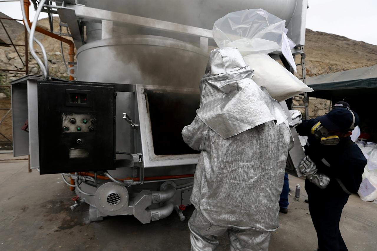An anti-narcotics worker burns a bag containing cocaine and other drugs during an incineration of about 14 tons of drugs seized during police operations, according to the Interior Ministry, in Lima, Peru, November 22, 2017. REUTERS/Guadalupe Pardo
