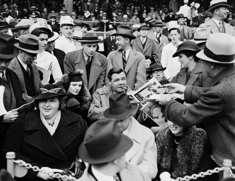 In this September 30, 1936, Works Progress Administration, Federal Writer's Project, photo provided by the New York City Municipal Archives, a man hands a program to baseball legend Babe Ruth, center, as he is joined by his second wife Clare, center left, and singer Kate Smith, front left, in the grandstand during Game 1 of the 1936 World Series at the Polo Grounds in New York. Over 870,000 photos from an archive that exceeds 2.2 million images have been scanned and made available online, for the first time giving a global audience a view of a rich collection that documents New York City life. (AP Photo/New York City Municipal Archives, WPA Federal Writers' Project) MANDATORY CREDIT