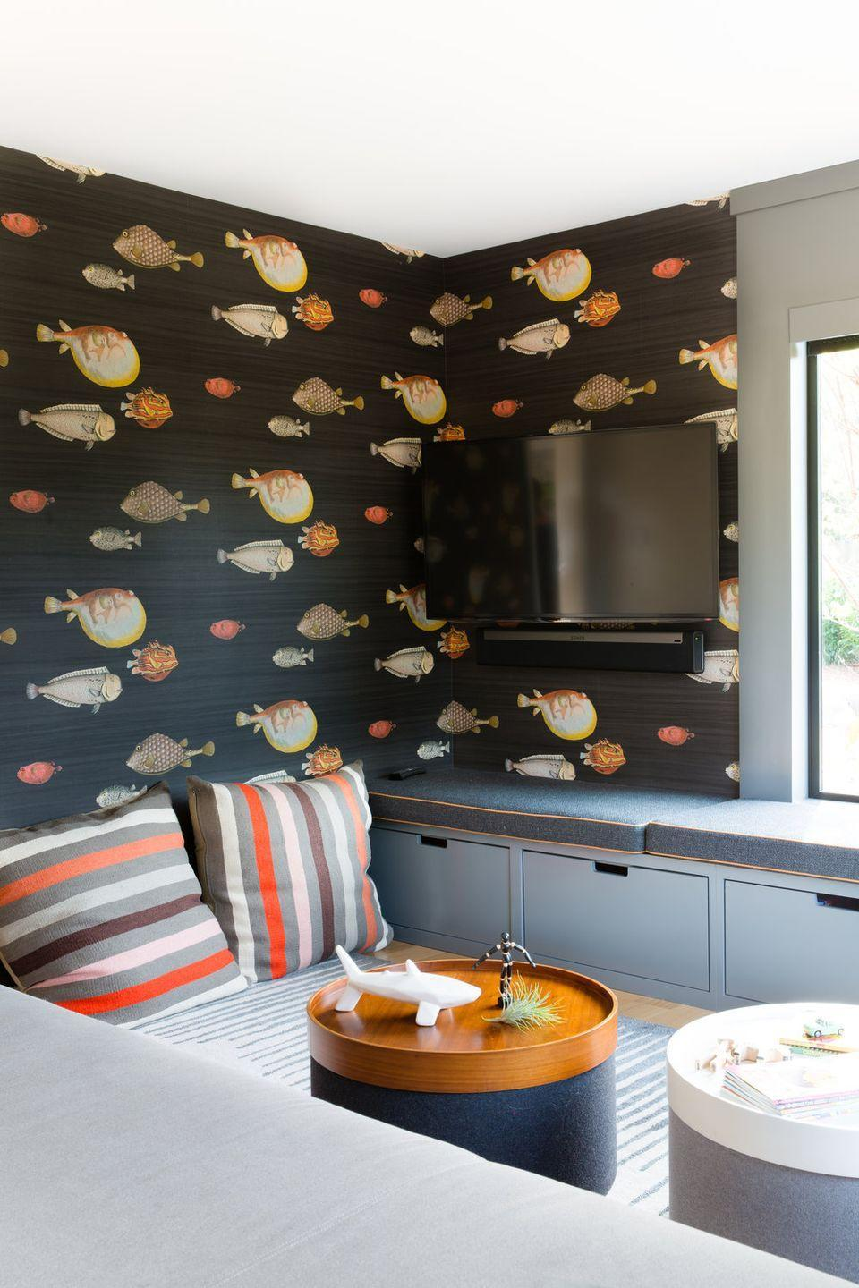 <p>With built-in storage under the extra bench seating, kid-friendly coffee tables, colorful floor cushions, and whimsical wallpaper, this media room is also quirky enough to be the backdrop for a playroom. </p>