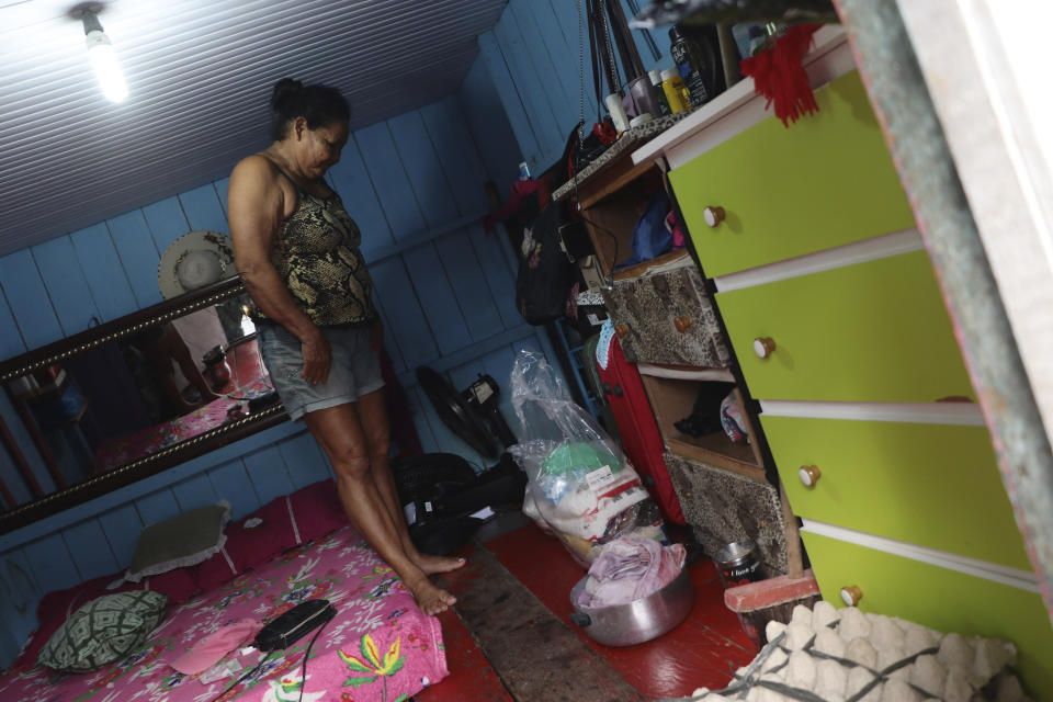 Noemia Ferreira Ribeiro stands on an elevated floor that was placed to avoid floodwater under her home in Anama, Amazonas state, Brazil, Thursday, May 13, 2021. (AP Photo/Edmar Barros)