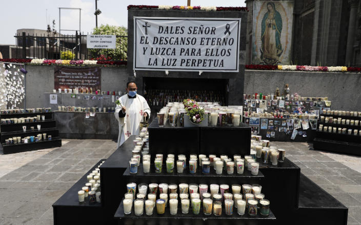 A priest blesses a memorial for COVID-19 victims installed outside the Basilica of Guadalupe in Mexico City, Wednesday, April 14, 2021. (AP Photo/Eduardo Verdugo)