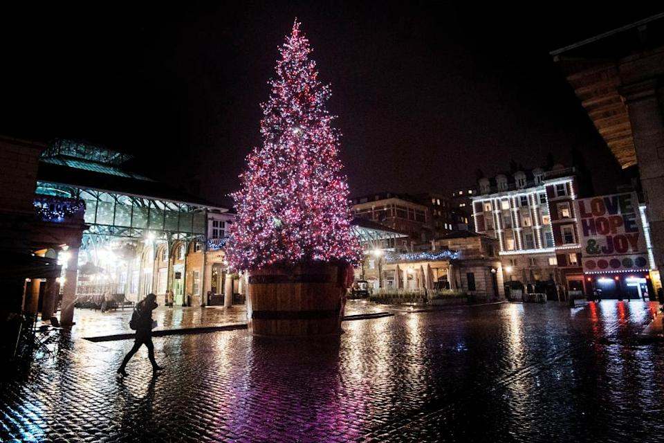 A Christmas tree lights up a quiet Covent Garden in central London.