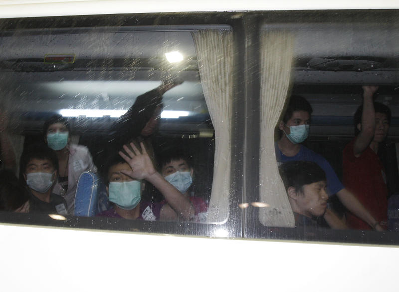 Taiwanese, suspected of being members of a fraud syndicate, wave from the window of their bus as they arrive at Manila's International Airport, Philippines early Wednesday Sept. 19, 2012. About 279 Taiwanese were deported following their arrest for alleged online fraud. One died while others began falling ill in crowded makeshift detention facilities, officials said. (AP Photo/Aaron Favila)