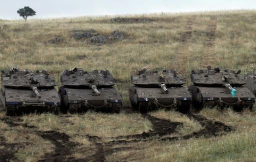 Israeli Merkava Mark IV tanks take position near the Syrian border in the Israeli-annexed Golan Heights on May 9, 2018