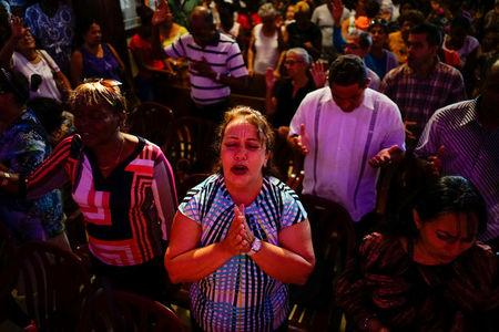 People react during a religious ceremony where victims of the Boeing 737 plane crash were remembered at a church in Havana, Cuba, May 20, 2018.  REUTERS/Alexandre Meneghini