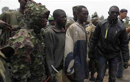 Congolese FARDC soldiers arrest two suspected rebels as they advance to a new position in Kibati