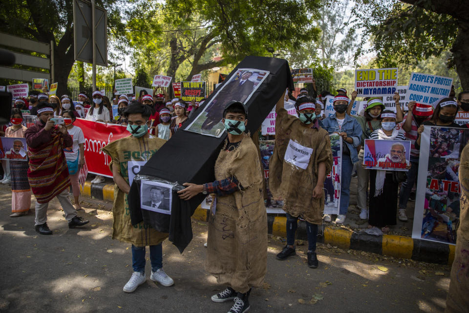 Chin refugees from Myanmar carries a mock coffin of Chinese President Xi Jinping during a protest against military coup in Myanmar, in New Delhi, India, Wednesday, March 3, 2021. (AP Photo/Altaf Qadri)