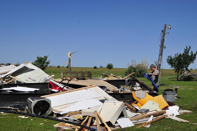 An El Reno, Okla. resident searches through the wreckage of a friend's mobile home hoping to find undamaged belongings in El Reno on Saturday June 1, 2013. (AP Photo/Nick Oxford)
