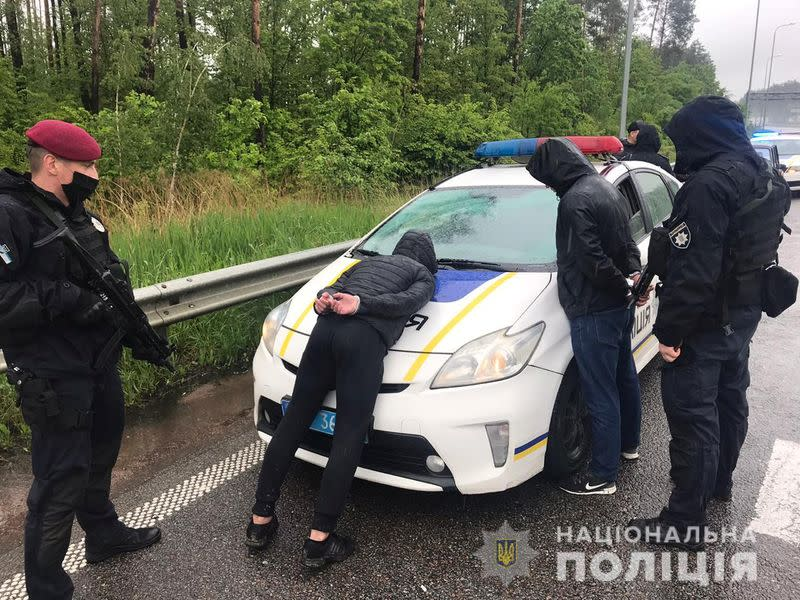 Police officers detain men suspected of taking part in a recent armed conflict in Zhytomyr Region