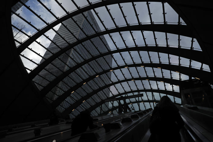 People use the escalator as they exit Canary Wharf underground station, with the JP Morgan building above them at left, in London, Thursday, March 25, 2021. (AP Photo/Alastair Grant)