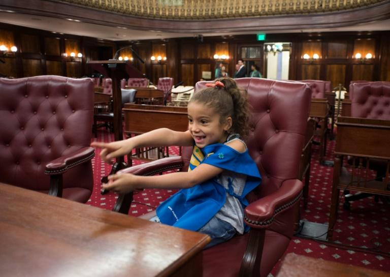 Mileny, a member of Girl Scout Troop 6000 checks out a seat in the City Hall Chambers in New York